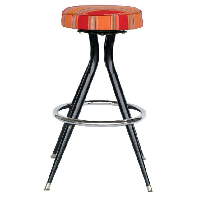 Set of three sharp black enamel steel swivel bar stools with original tricolor cloth seat covers.