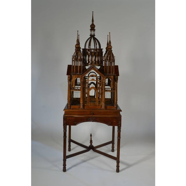 """A continental carved mahogany """"Cathedral"""" bird cage, modelled with central dome, towers at each corner, each side with..."""