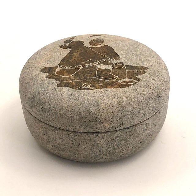 The lid of this charming Inuit soapstone trinket box, signed Siku, features a figure ice fishing. His or her parka and...