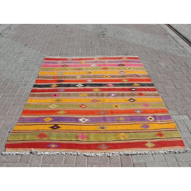 Offered is a vintage handwoven Turkish kilim rug. The kilim is nearly 55 years old. It is handmade of very fine quality...