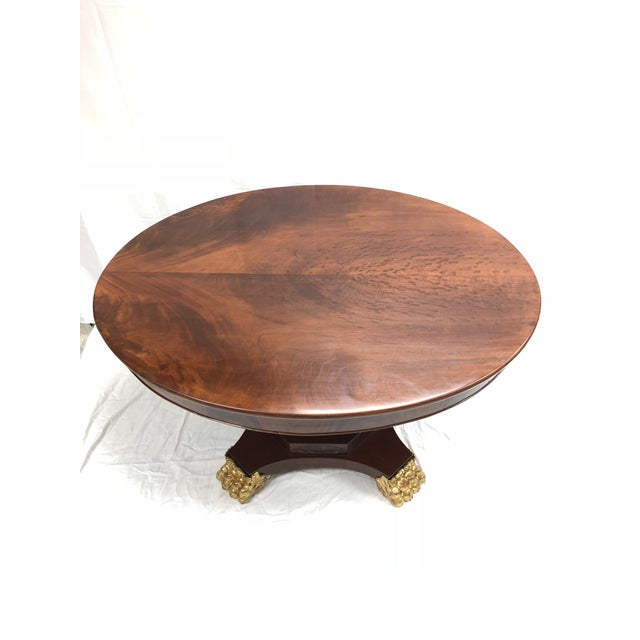 A handsome 19th Century English Regency flamed mahogany and gildwood oval table.The table is raised by finely carved...