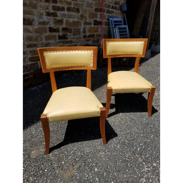 Pair of Yellow leather side chairs with modern lines and shiny decorative racks.