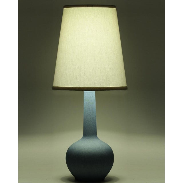 """A lake blue crackle finish ceramic table lamp with ivory linen shade made in the US. Shade dimensions: 10"""" x 14"""" x 16"""""""