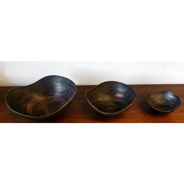A gorgeous set of Italian modern pottery nesting bowls by Raymor. All bowls are signed and sequentially numbered; a great...