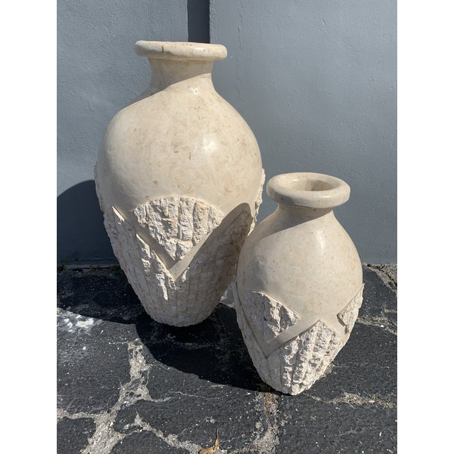 Organic, post modern style pair of Mactan stone floor vases. Consisting of textured stone wrapped around vases. Mark on...