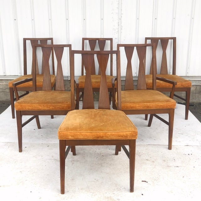 This beautiful mid-century dining set features a rich walnut finish with sculpted seat backs and ovular dining table. The...