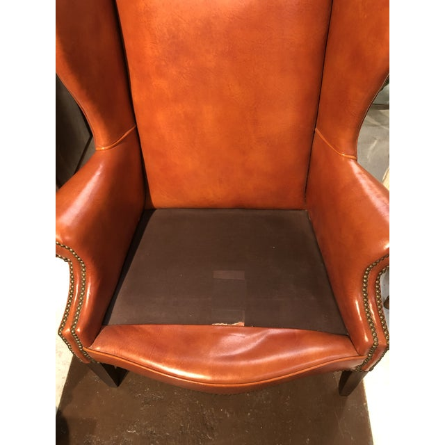 Vintage Georgian style gentleman's orange leather arm chair with brass tacks and stretcher. The cushion on this arm chair...