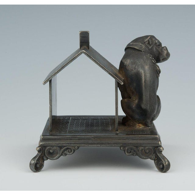 Seated by his dog house, the bulldog casts his gaze warily over one shoulder. This functional piece is set on a squared...