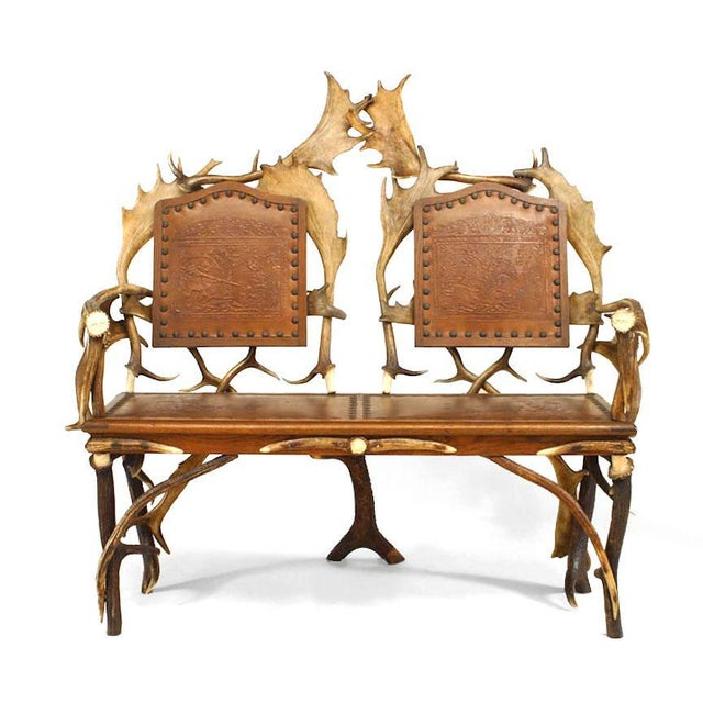 Rustic German (19th century) oak and antler loveseat with carved medallions on arms and brown embossed leather seat & back...