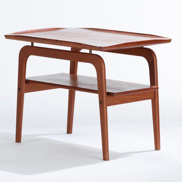 Pair of Danish modern teak and brass side tables designed by Arne Hovmand Olsen. Circa 1960s. Tables have 2 tiers with the...
