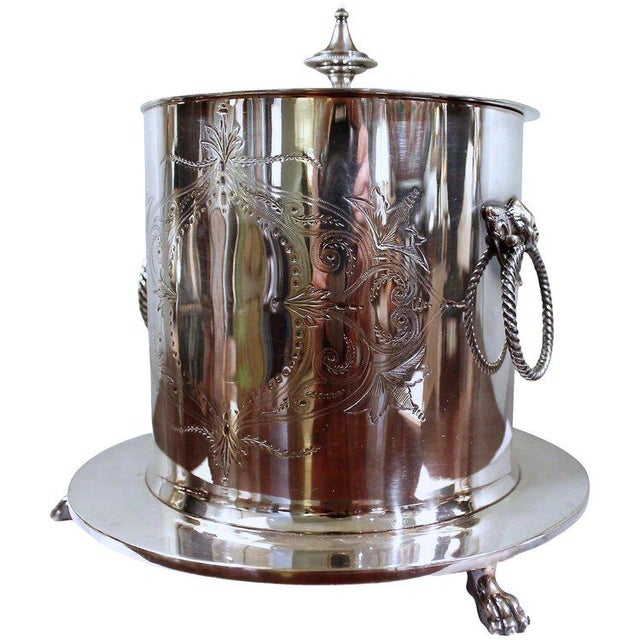 A good silver on brass ring handled biscuit box, resting on a paw footed plinth. English or American, ca. 1890, with...