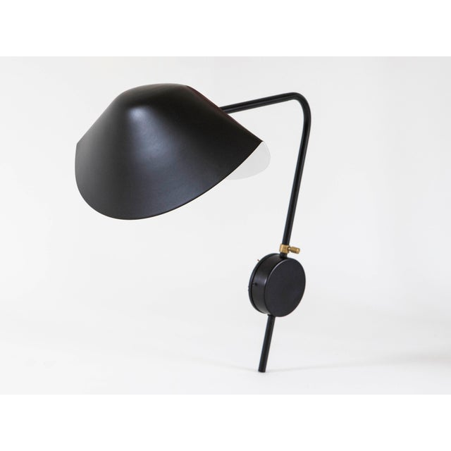 Serge Mouille single arm black Antony sconce, 2013 edition by Gueridon. The mussel-shaped shade is connected by a brass...