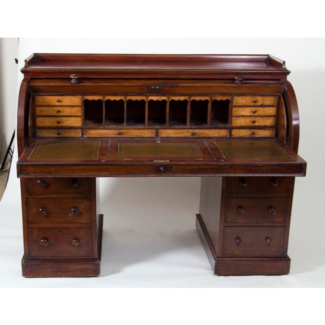 A fantastic antique English mahogany roll top desk with fitted birds eye maple interior. Made by Richards and Co in London...