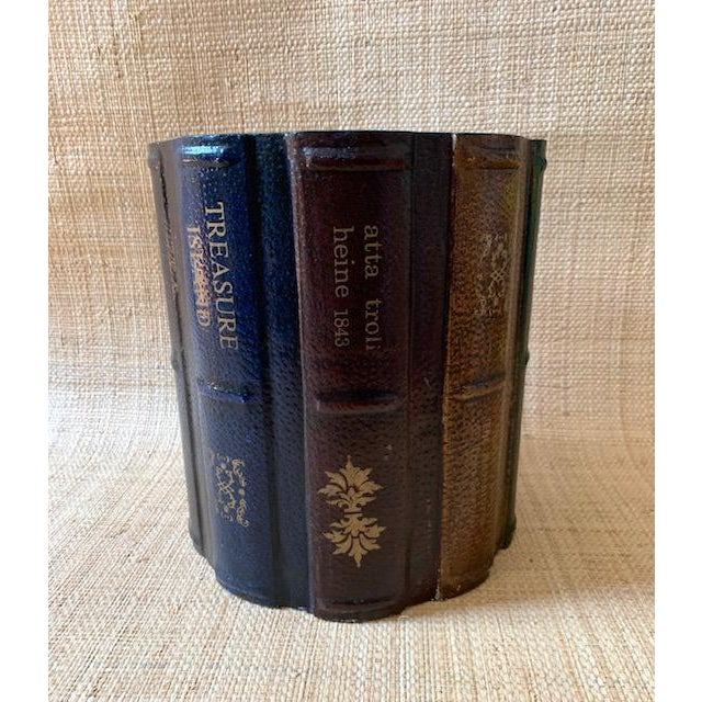 Wood carved Faux leather spines surround the exterior of this wastebasket. The book titles are Treasure Island and Mark...