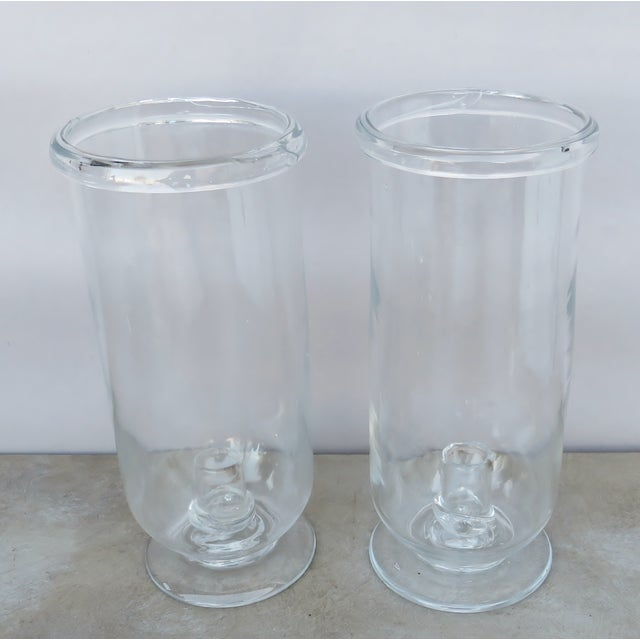 A pair of rustic-style blown glass tall hurricanes. Uses one taper candlestick, each. No maker's marks, pontil on undersides.