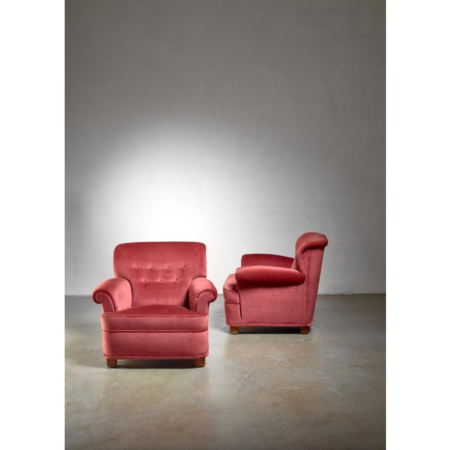 A pair of comfortable model 'London' easy chairs by Carl-Johan Boman for Oy Boman Ab. The chairs have a fresco red fabric...