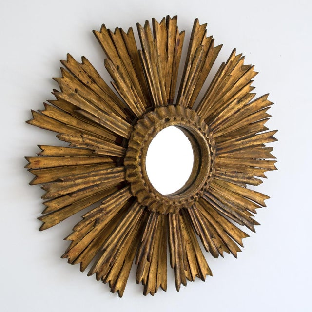 A large mid-century decorative wooden sunburst mirror with beautiful original time worn gilded patina and featuring rays...