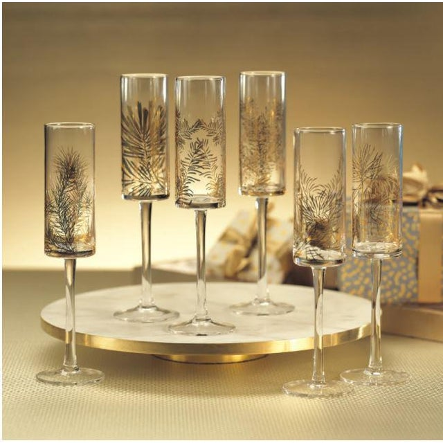 Fabulous set of twelve champagne flutes adorned with six different evergreen tree branch design. Mixed set with two of...