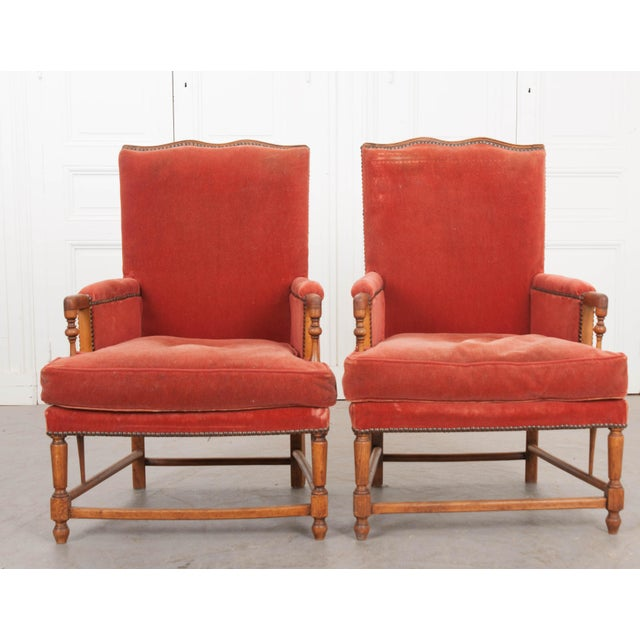 This fabulous pair of French Provincial walnut fauteuils, c. 1870. From France and are covered in a deep coral velvet...