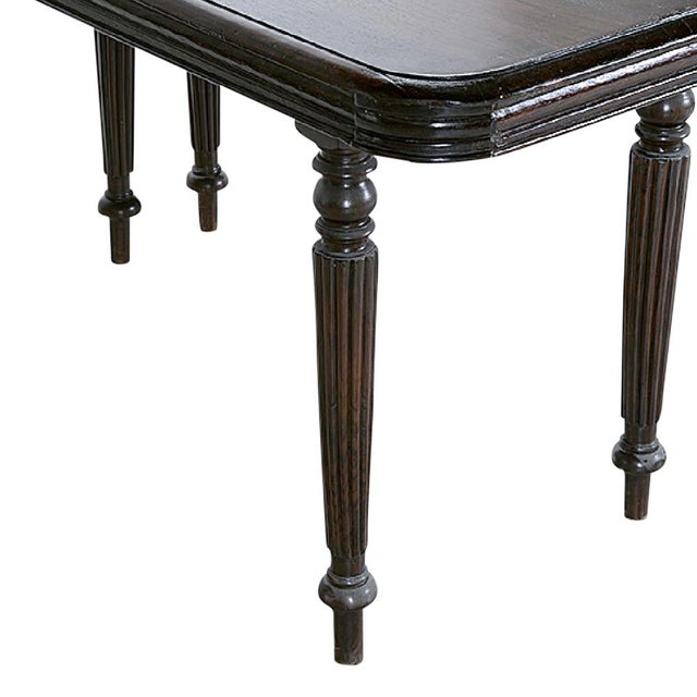 This charming pair of Anglo Indian demi-lune tables stand on reeded legs, have a carved apron, and are made of natural...