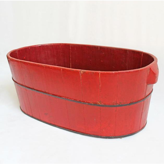 Red painted wood barrel container with iron support rings. Great for use as a large planter container.