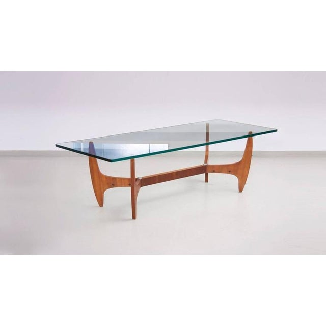 Highly decorative midcentury coffee table with heavy and thick glass top. The base is produced in beautiful grainy wood...