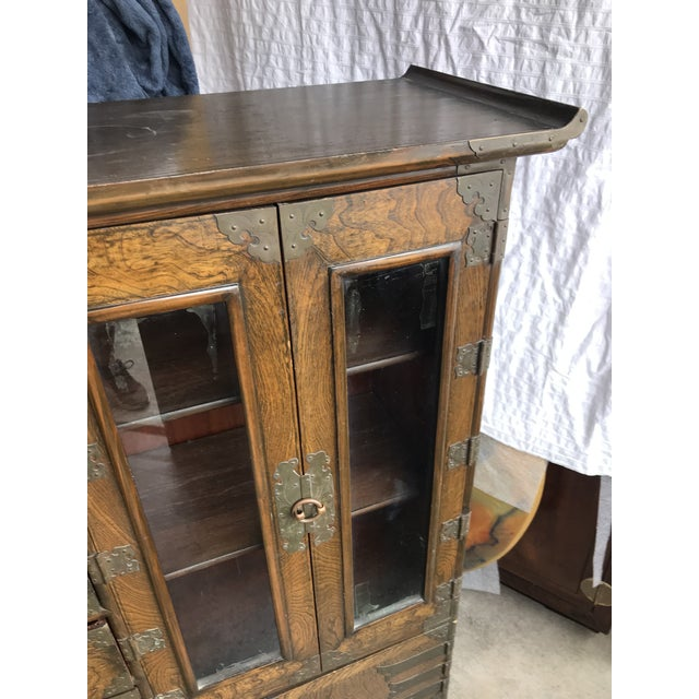 A George III Chinoiserie style brass-mounted elm armoire cabinet. From the first half 20th century. The rectangular top...