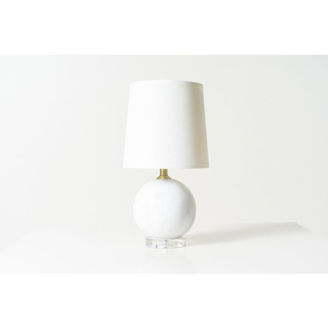 Small table lamp with white marble sphere on lucite base.