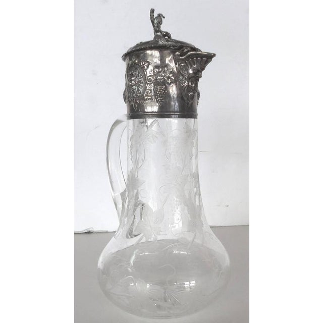An elegant 19th century claret jug fitted with an ornate repousse sterling silver spout and lid. The silver designs...