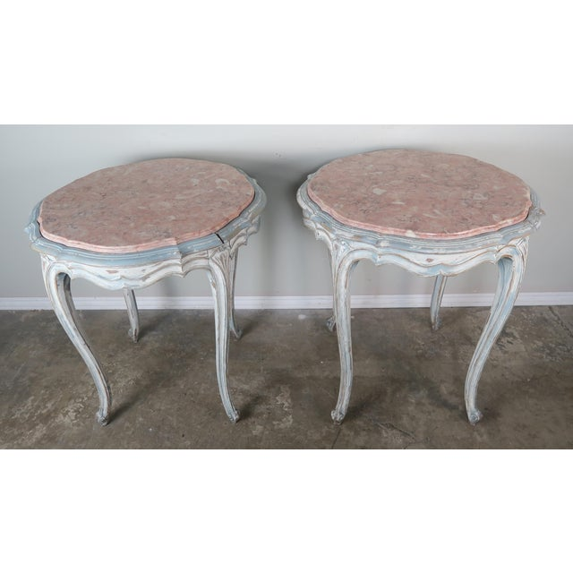 Pair of French Louis XV style painted round shaped tables with inset marble tops. The tables are painted in a worn dove...
