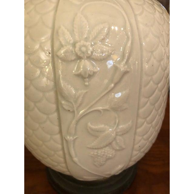 Elegant pair of vintage jar shaped ceramic blanc de chine lamps having lovely raised patterns and wooden bases. New custom...