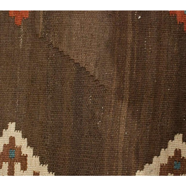 An early 20th century Persian Shahsavan runner with multiple crimson and indigo diamond patterns on a natural wool...