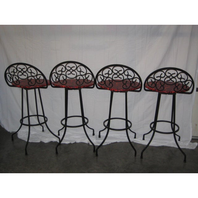 Mid century set of four ornate Arthur Umanoff iron bar stools in all original excellent condition. The vinyl is a...