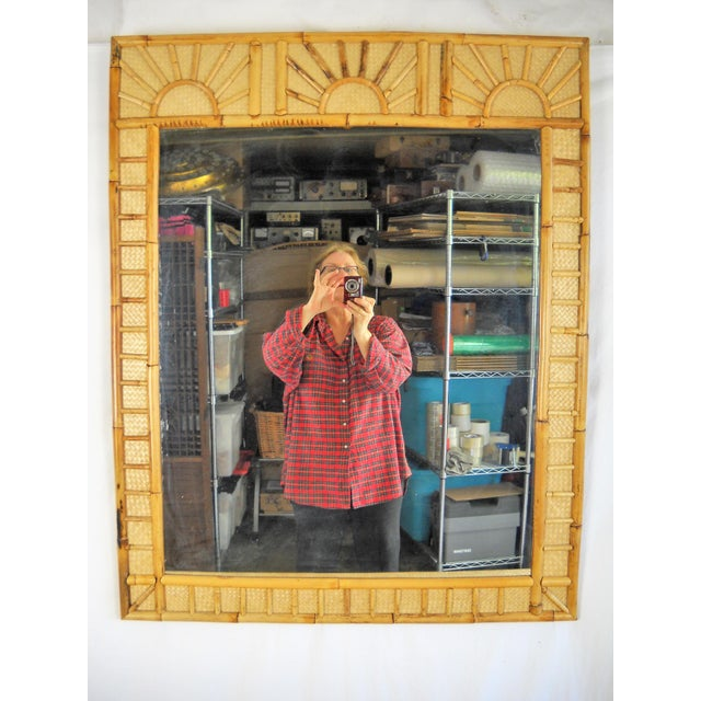 """Lovely bamboo and raffia covered mirror featuring a """"sunrise"""" bamboo design, circa 1970's. Expertly crafted wood case..."""