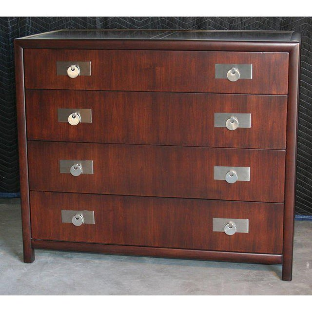 Elegant chest of drawers by Michael Taylor for Baker Furniture. Dark stained cherry with nickel plated pulls. Finished on...