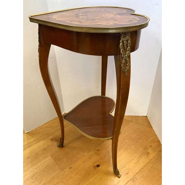 Unique heart shaped two tiered table features a beautiful marquetry inlay on top and bronze ormolu mounts. Made in Italy.