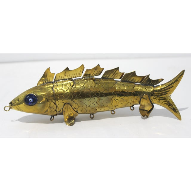 Stylish brass artisan made articulated fish sculpture with engaging hand made eyes. Created mid century in Malta.
