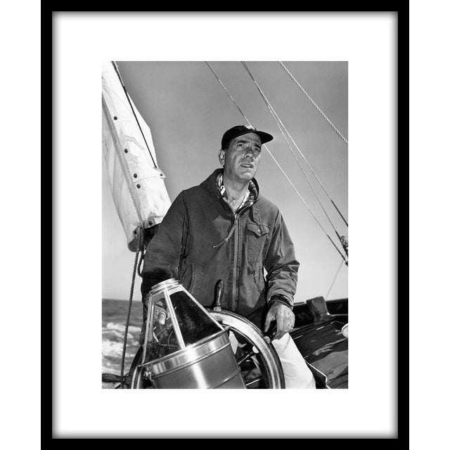 "Humphrey Bogart at the helm of his yacht Santana, 1952. ""11"" x 14"" silver gelatin fiber based print signed on verso by the..."