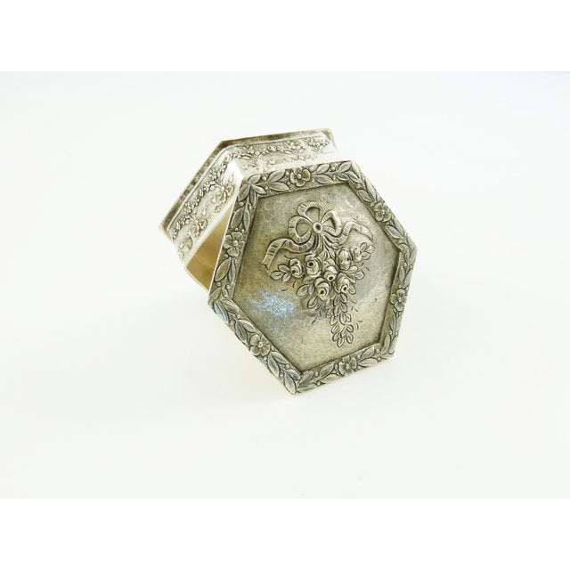 An estate French sterling silver box. The hexagon shaped box is decorated on the top with ribbon and a large spray of...