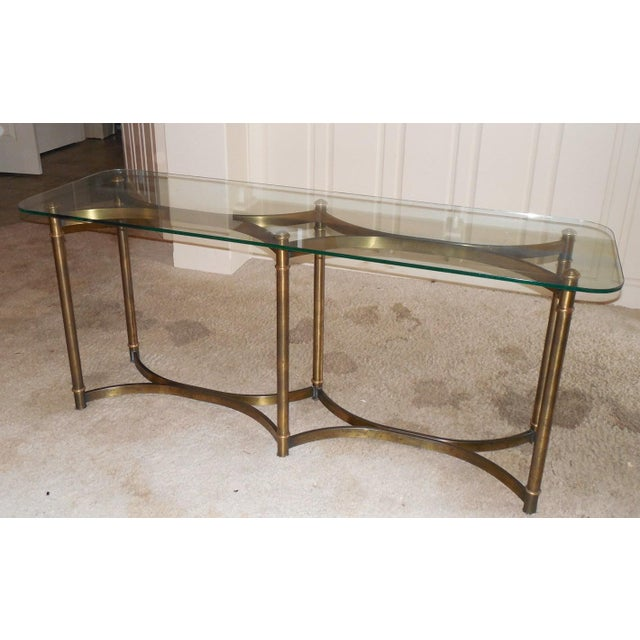 A wonderfully versatile and timeless burnished brass and glass console with elegantly curved double stretchers in the...