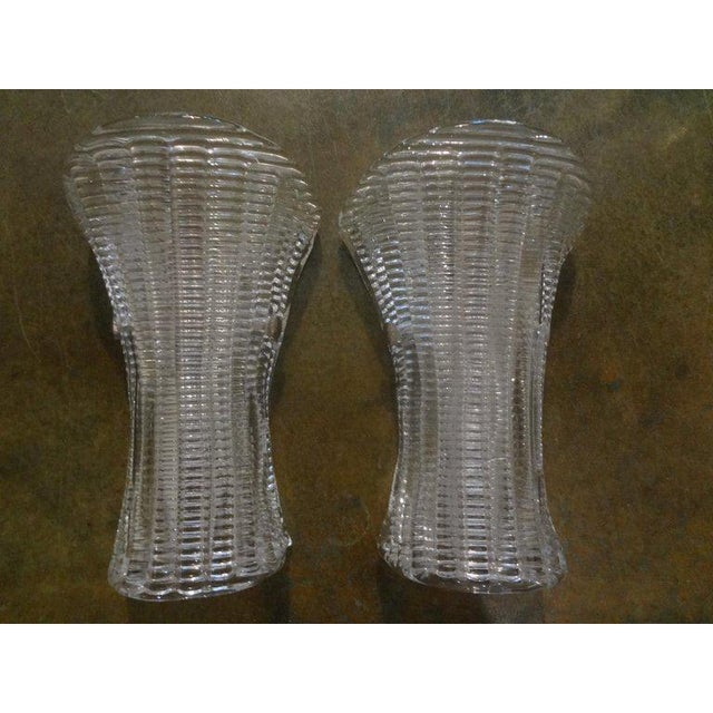 Stylish pair of Mid-Century Modern Murano glass sconces with chrome frames. This pair of Hollywood Regency Murano glass...