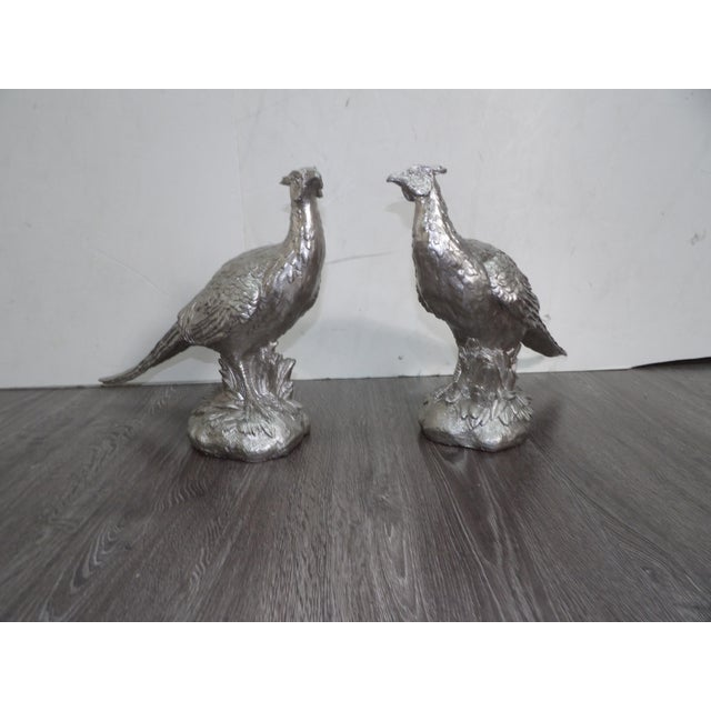 Largepair of composite figurines Pair of pheasants.The Pair have a boldnew coat of silver paint.The pair are on display in...