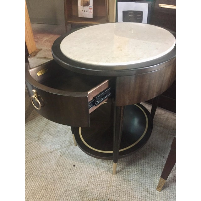 his small round side table is a vision in white marble and bronzed ebony-finished wood. This piece is perfect for resting...