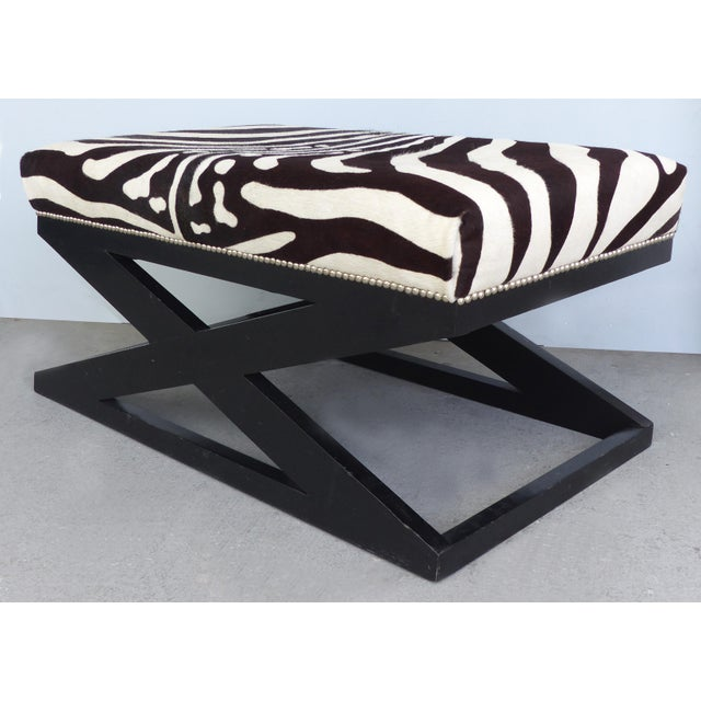 """Offered for sale is a zebra print upholstered ottoman in the """"Bel Air"""" model by Barclay Butera Home. The X-shaped ebonized..."""