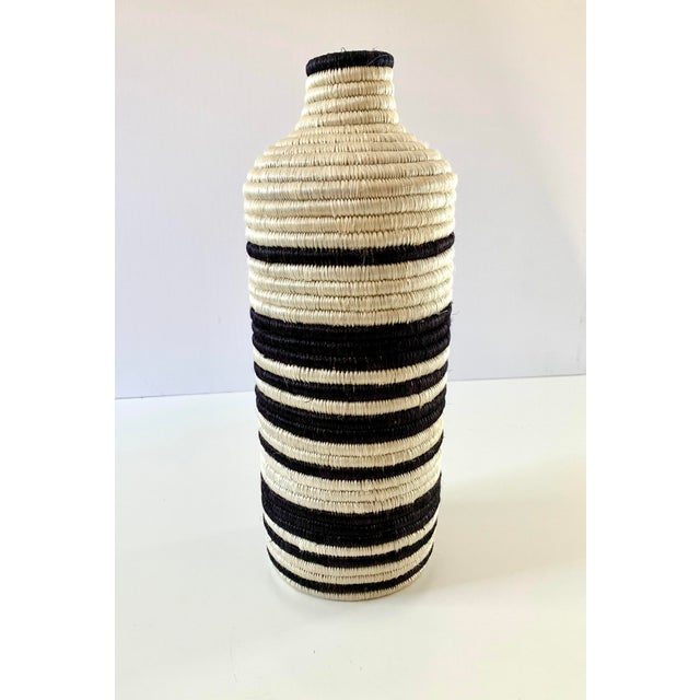 Intricately crafted black and white striped vase. Handwoven in Rwanda with all-natural fibers of raffia and sweet grass,...