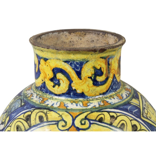 Globular shape decorated with yellows and blues with central cherub and a variety of other decoration. Signed on side of...