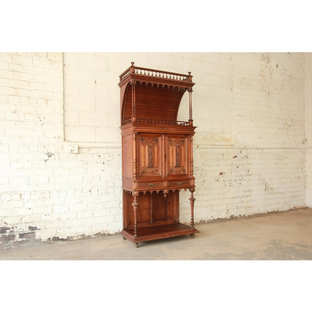 Offering a very nice antique carved oak tall French bar cabinet. This unique piece has beautiful carved details with...