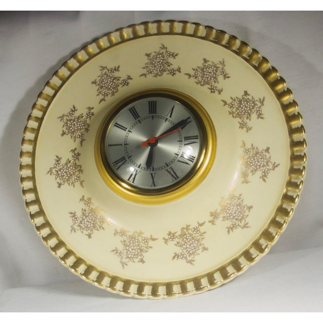 Electric wall clock with raised face. Ivory porcelain with hand painted gold leaf and white bead flowers. Clock face is...