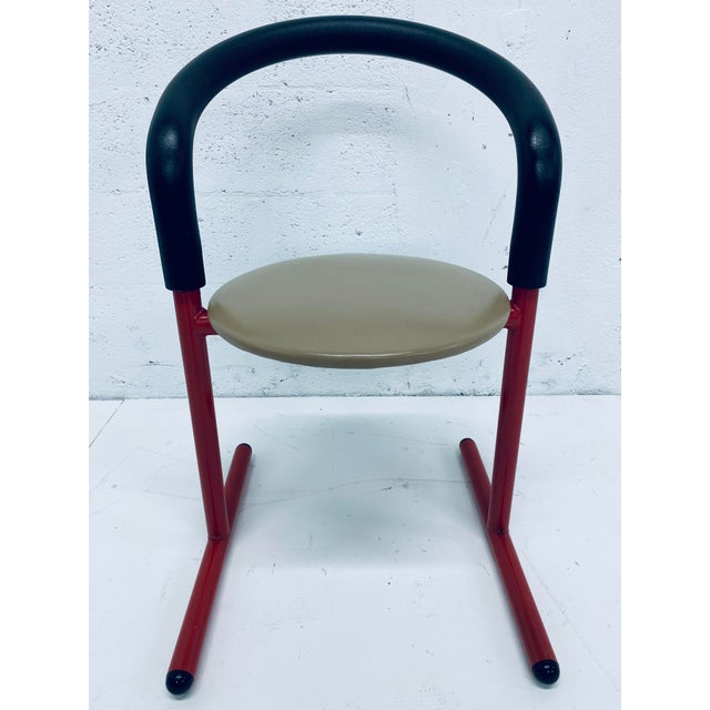 Tubular steel frame in red lacquer with black foam back support and beige seat cushion by Amisco, Canada.