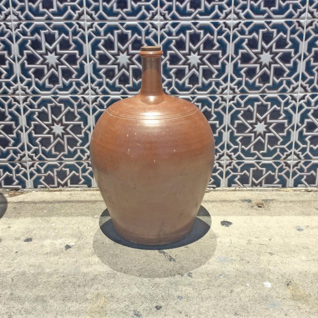 Brown glazed pottery vase with a round base and narrow neck. Vintage, handmade, and comes from France. Perfect for use as...